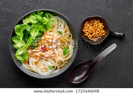 Guay Tiew Gai Cheek or Thai Chicken Noodle Soup in black bowl on dark slate backdrop. Guay Tiew Gai is Thailand cuisine soup with rice noodles, chicken meat, sauces, greens. Thai food. Top view