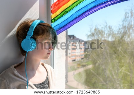 Sad teenage girl in headphones listening to music, leaning on the window. Misses her friends. Quarantine self-isolation. Copy spase #1725649885