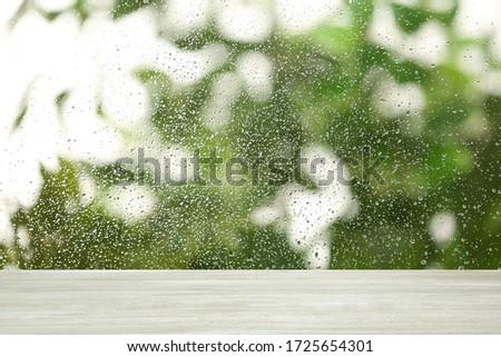White wooden table near window on rainy day