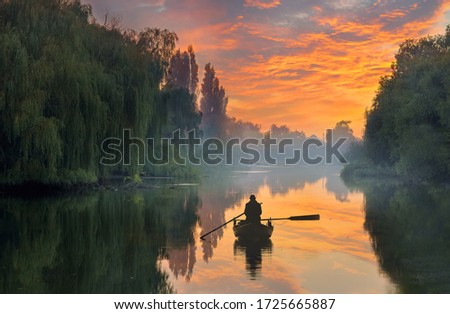 Fishing in a quiet evening on the river, fishing, in the distance haze, and the village, forest