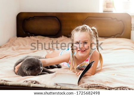 A little girl with blond hair lies on a bed at home with a cat reading a book. Stay at home. Home education for children. #1725682498