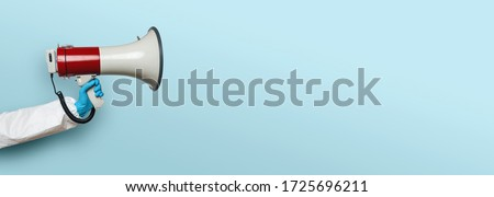 hand of medic or Nurse with gloves and a megaphone in front of an empty blue background, banner size, with copyspace for your individual text. Royalty-Free Stock Photo #1725696211