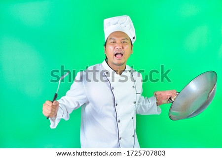 Chef wears cooking hat holding a pan and the spatula and shout on over green screen background.