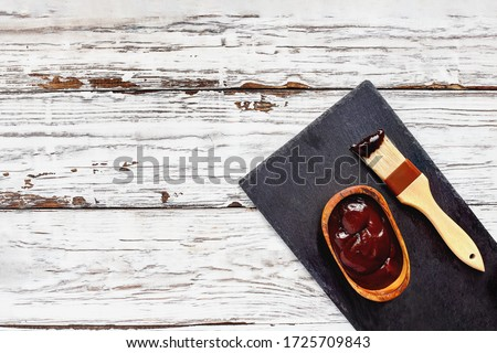 BBQ sauce in a wood bowl with brush over top a white rustic wood table / background with free space for text Image shot from overhead view.