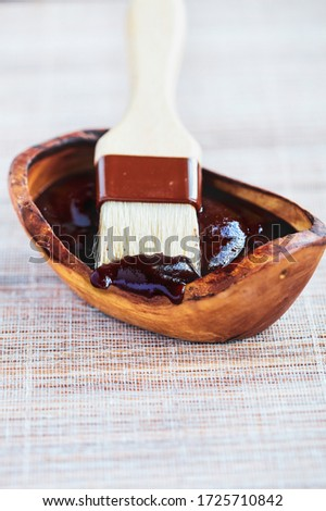 BBQ sauce on the tip of a basting brush with a wooden bowl filled with the condiment. Selective focus with blurred background.