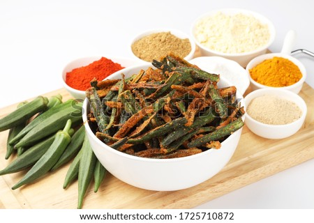 Bhindi kurkure or crunchy okra or ladies' fingers, a Rajasthani traditional dish served in a ceramic bowl  on wooden board along with ingredient for the recipe