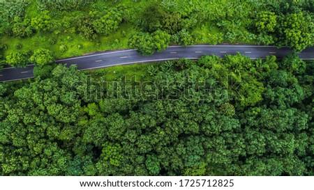 Aerial view asphalt road through green tropical rainforest nature landscape #1725712825