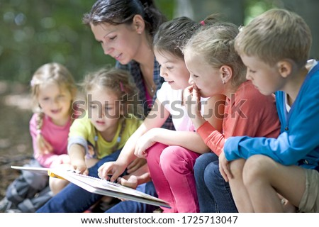 Kindergarten teacher reading with kids in a wood kindergarten Royalty-Free Stock Photo #1725713047