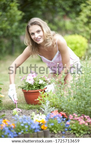 Portrait of young woman digging soil for plant in garden #1725713659