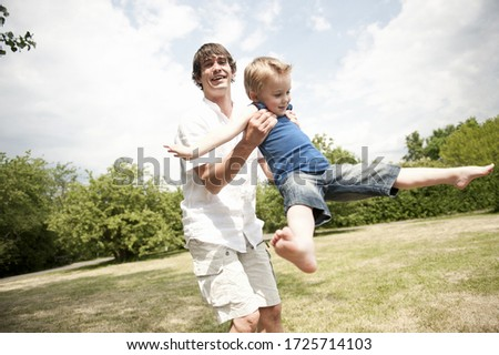 father spinning son around in park #1725714103