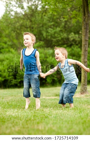 Twin brothers jumping and smiling in park #1725714109