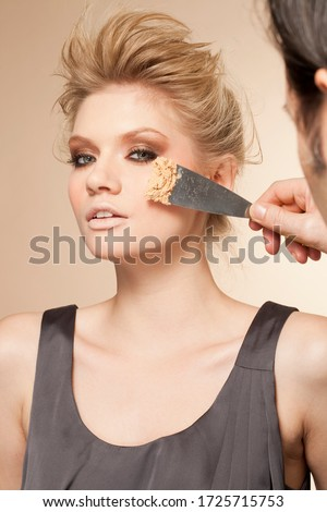 Portrait of young woman having make up applied by trowel #1725715753