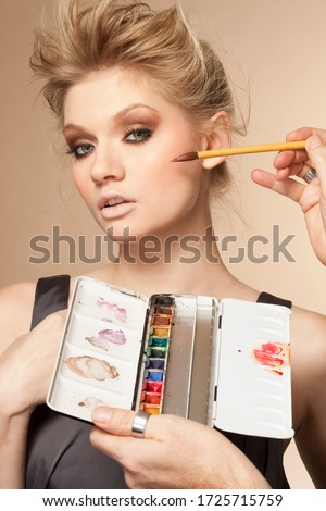 Portrait of young woman having make up applied in studio #1725715759