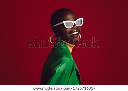 Beautiful woman wearing stylish sunglasses and smiling against red background. African female model wearing funky sunglasses. #1725716317