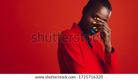 Glamorous female model on red background. African woman with buzz cut hairstyle and vibrant makeup looking at camera. Royalty-Free Stock Photo #1725716320
