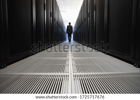 Rear view of businessman walking in server room in Cape Town, South Africa #1725717676