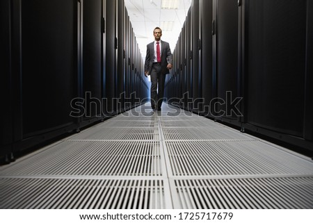 Businessman walking in server room in Cape Town, South Africa #1725717679