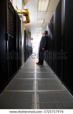 Businessman standing in server room in Cape Town, South Africa #1725717976