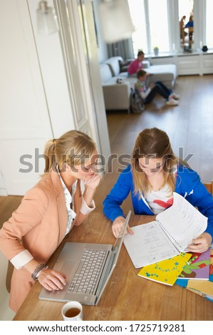 High angle view of mother helping daughter with homework at dining room table #1725719281