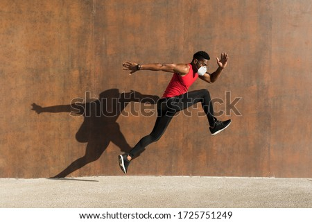 Powerful athlete training with n95 face mask for protecting against Covid-19. Young black man running and jumping casting shadow on a wall. #1725751249