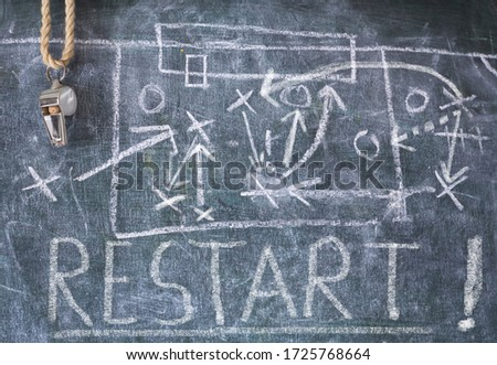 Restarting soccer sport after the coronavirus lockdown, symbolic picture with referee's whistle, blackboard strategy diagram and message