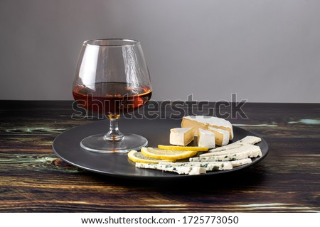 Cognac in a glass and an appetizer for cognac (Camembert cheese, blue cheese and lemon). Appetizer for alcohol, dear spirits. Royalty-Free Stock Photo #1725773050