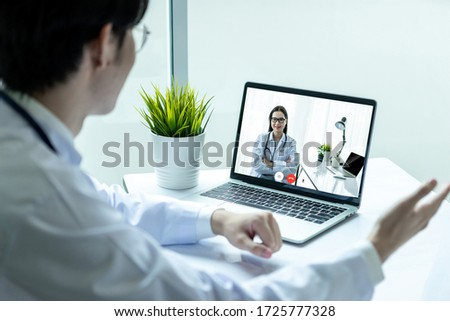Asian doctor man wearing stethoscope white coat video call with woman doctor in his office. #1725777328