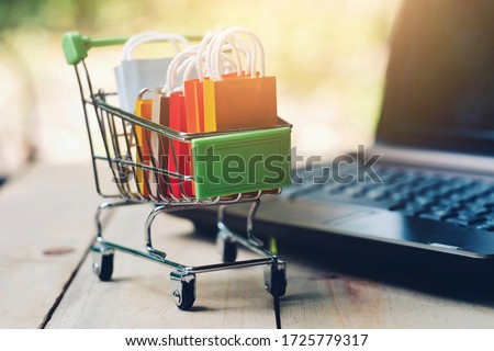 close up toy shopping cart with small bag and computer on table, e-commerce and online business technology, global pandemic and economic crisis, new normal, stay and work from home concept Royalty-Free Stock Photo #1725779317