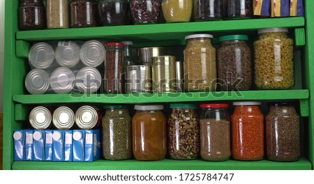 Buying food in bulk during the coronavirus lockdown period. Home pantry shelves with long-term storage and canned products