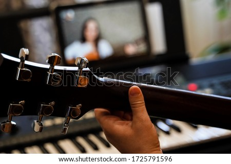 virtual guitar lesson. female musicians play together online in isolation because of the coronavirus pandemic #1725791596