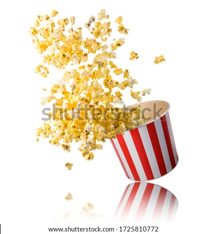 Flying popcorn from paper striped bucket isolated on white background with clipping path. Concept of cinema or watching TV. #1725810772