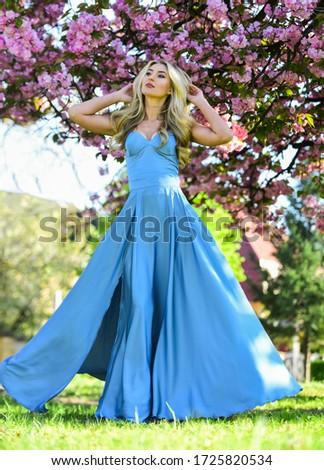 Pretty blonde fancy woman. Femininity. Sakura season. Gorgeous girl. Spring fashion collection. Woman fancy dress gown spring flower sakura bloom. Girl in cherry flower blossom. Sakura tree blooming. #1725820534
