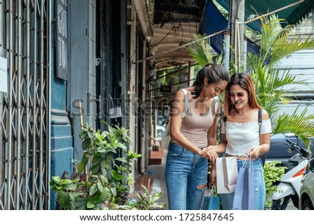 Two girls looking inside shopping bag stock photo
