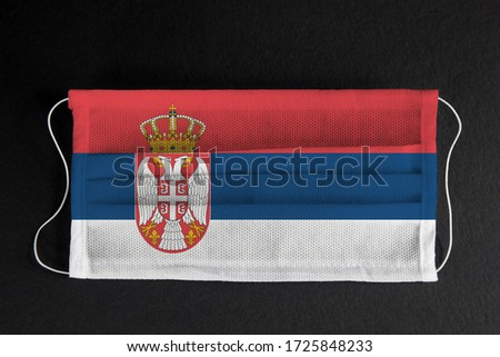 Coronavirus covid pandemic in Serbia. Flag of Serbia printed on medical mask on black background. National healthcare system concept. Covid-19 outbreak, quarantine in Belgrade, Serbia #1725848233