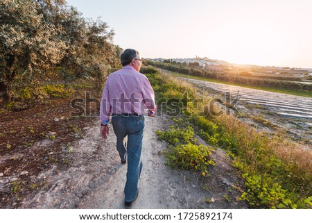 Older man walks alone on the street after being confined by coronavirus. Blurred edges. #1725892174