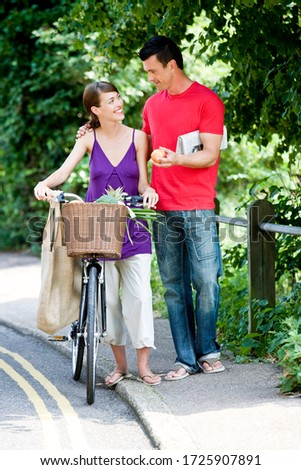 A man and woman walking together with a bicycle and shopping #1725907891