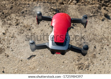 Small sized red drone with high resolution camera hovering in air for aerial photography.