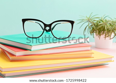 Stylish eyeglasses over pile of books. Studing, reading, optical store, eye test, vision examination at optician, fashion accessories concept. Front view  Royalty-Free Stock Photo #1725998422