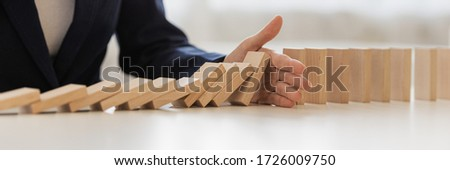 Wide view image of hand of businesswoman interrupting collapsing dominos in a conceptual image of preventing financial and market depression. #1726009750