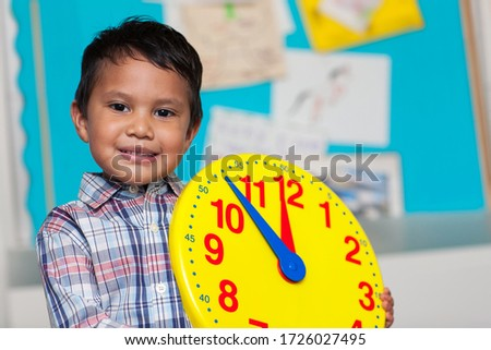 Young boy with a preppy shirt, holding a big analog clock with a colorful bulleting board in the background.