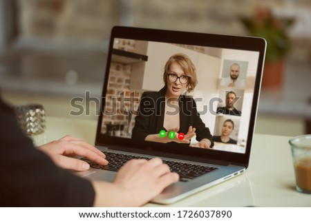 A laptop screen view over a woman's shoulder. A girl listening as a boss gives a task on an online briefing on a computer in her studio. A student listening to a female professor in an online lecture. #1726037890