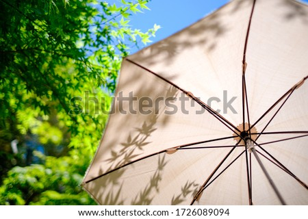 White parasol in the summer sunshine Royalty-Free Stock Photo #1726089094