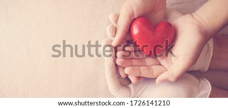 Doctor hands with medical gloves holding child hands and red heart, health insurance, donation, charity during covid-19 coronavirus pandemic, saving life, thank you and appreciation to doctor #1726141210