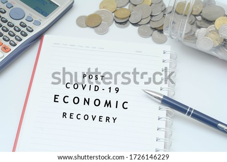 "Post covid-19 economic recovery conceptual. Top view of an image with 'POST COVID-19 ECONOMIC RECOVERY"" text on the book with calculator, coins spilling out of from jar and pen. #1726146229"