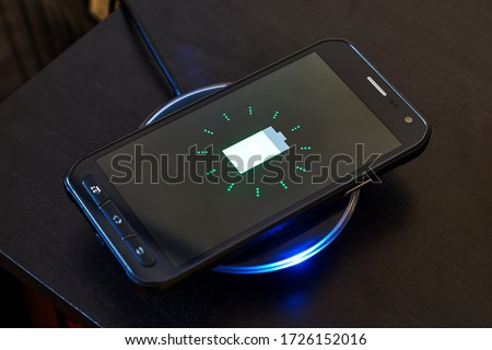 An Android smartphone charges its battery by resting on top of a wireless charging pad. Wireless charging is done via electromagnetic induction. Royalty-Free Stock Photo #1726152016