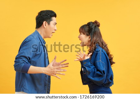 Profile side view portrait of two attractive angry aggressive nervous people having fight anger blame isolated over vivid shine bright orange background. Negative emotions concept. Royalty-Free Stock Photo #1726169200