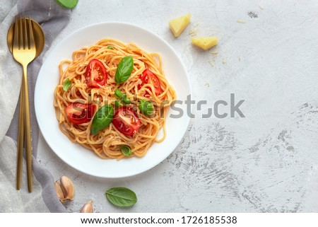 Pasta with cherry tomatoes, cheese and basil on a light background. High key, top view, copy space #1726185538