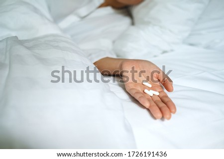 Closeup image of a sick woman sleeping and lying down on a bed with white pills in hand #1726191436