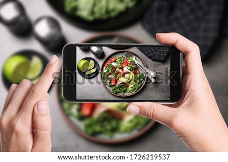 Blogger taking picture of delicious salad with prosciutto at table, closeup. Food photography