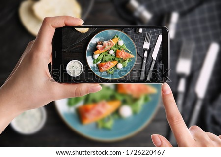 Blogger taking picture of fresh melon with prosciutto at table, closeup. Food photography